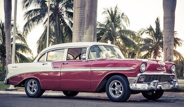 Zabytkowy Cadillac w kolorze czerwono białym, pod palmami na Florydzie.