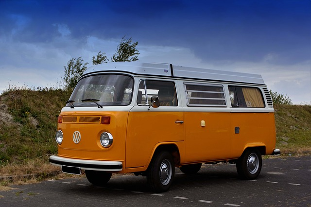 Zabytkowy Volkswagen T1 z 1967 roku w pomarańczowo białym kolorze, na parkingu przy plaży